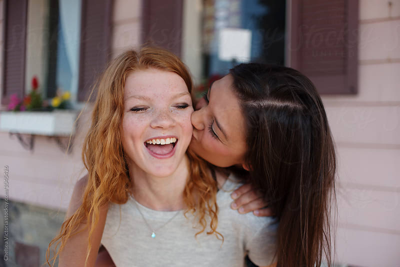Teenage sisters on a city street in the summertime by Chelsea Victoria for Stocksy United