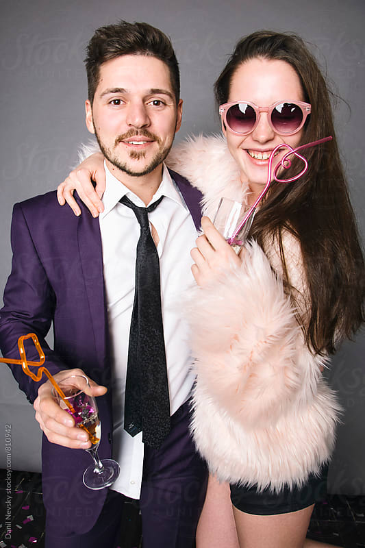 Photo of beautiful young couple holding glasses of champagne by Danil Nevsky for Stocksy United