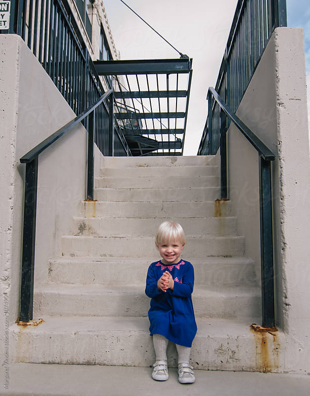 happy little girl on stairs by Margaret Vincent for Stocksy United