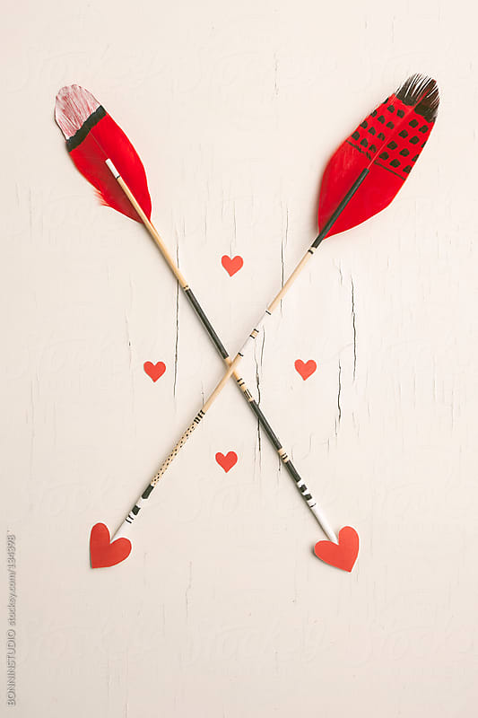 Two arrows with red feather and hearts for Valentine's day. Hipster symbol. by BONNINSTUDIO for Stocksy United