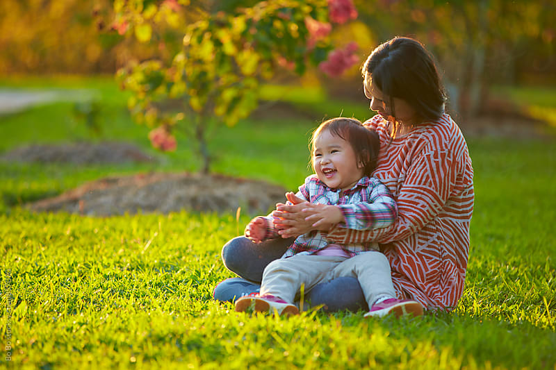 happy little girl with her mother outdoor in the sunshine park by cuiyan Liu for Stocksy United