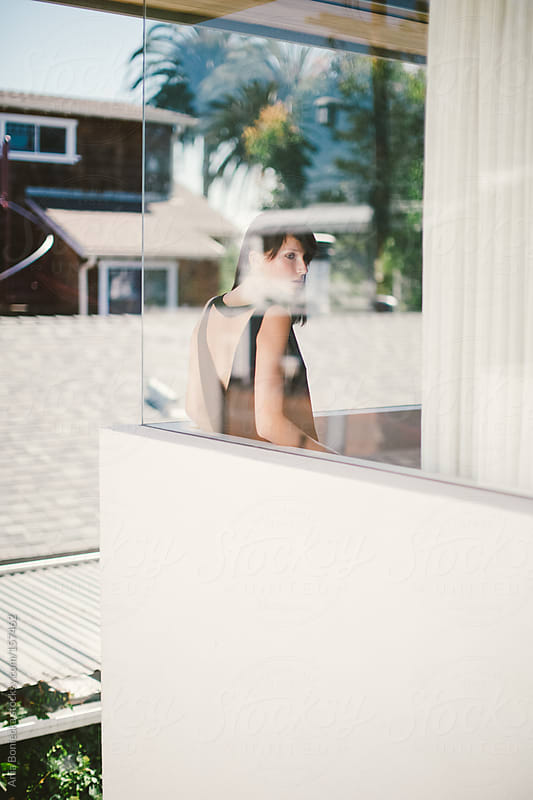 A beautiful woman standing by a house window by Ania Boniecka for Stocksy United