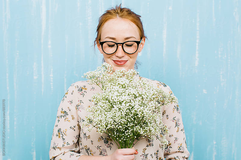 Smiling ginger woman holding a bouquet of flowers. by BONNINSTUDIO for Stocksy United
