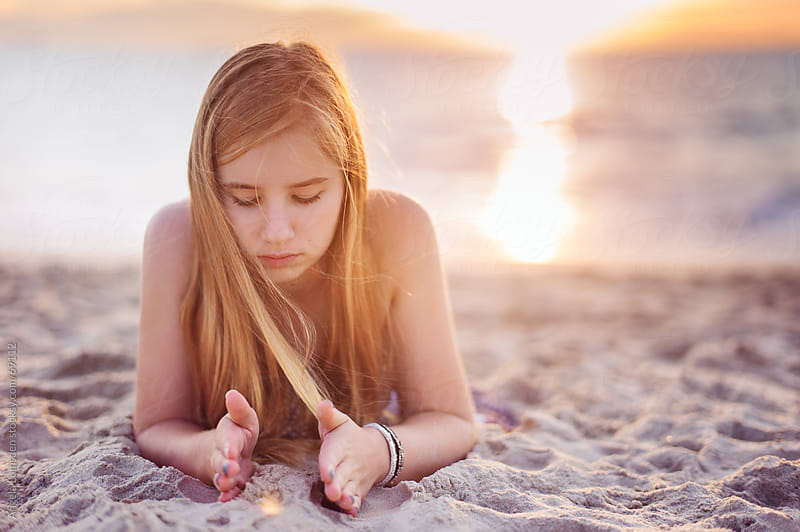 Girl playing with sand at the beach at sunset by Angela Lumsden for Stocksy United