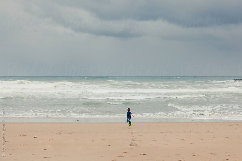 Boy on the beach running to the ocean on a stormy summer day by Cindy Prins for Stocksy United