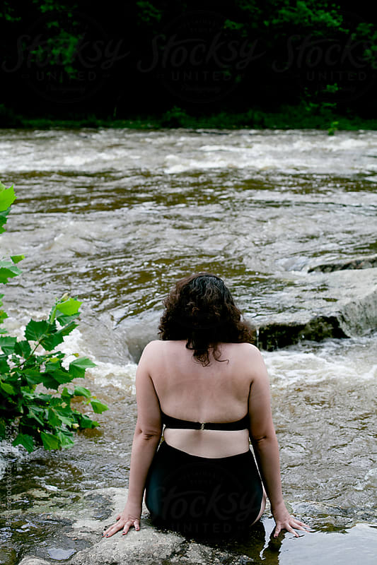 Woman in retro bikini relaxing in river  by Jennifer Brister for Stocksy United