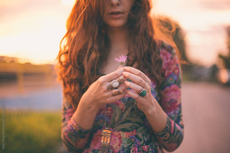 Pretty girl in floral dress holding the flower at sunset. by Nabi Tang for Stocksy United