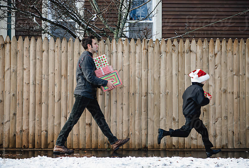 Boy runs ahead of his dad as they carry Christmas presents by Cara Dolan for Stocksy United