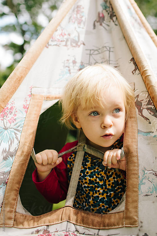 Close up of little girl looking out of the window of a play tent. by Julia Forsman for Stocksy United