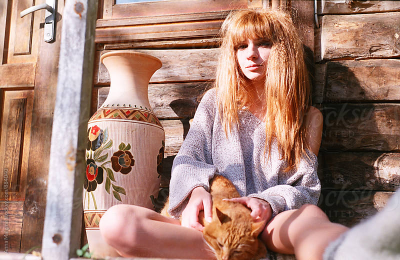 A portrait of young redhead woman in front of old russian wooden house with a redhead cat by Anna Malgina for Stocksy United