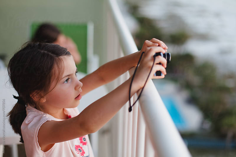 Young girl taking photo from the balcony at a beachfront highrise by Amanda Worrall for Stocksy United