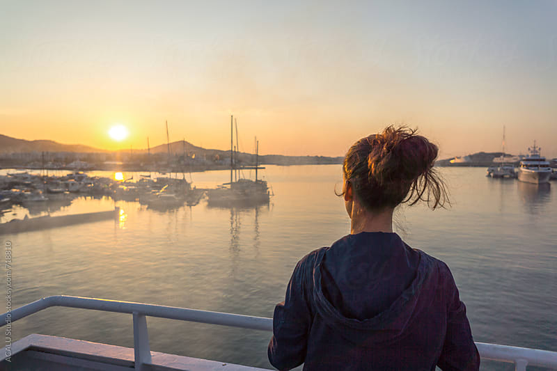 Young woman watching beautiful sunrise at port by ACALU Studio for Stocksy United