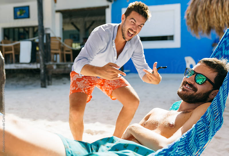 Young man photobombing and bothering his friend who is resting on a hammock in the beach by Alejandro Moreno de Carlos for Stocksy United