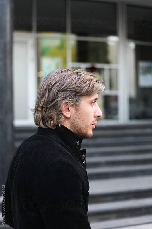 Handsome man in black jacket in the street  by Marija Mandic for Stocksy United