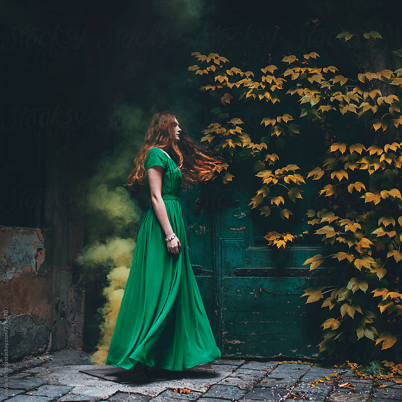 Young woman in a long green dress dancing by Jovana Rikalo for Stocksy United