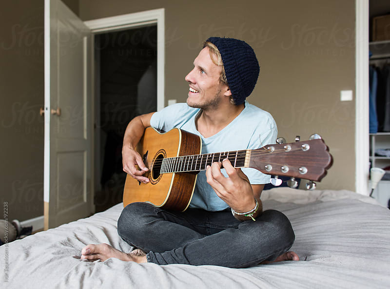 Young man sitting on his bed playing guitar, relaxing by Ivar Teunissen for Stocksy United