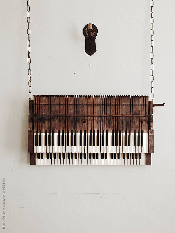old piano hanging from chains against white wall by Nicole Mason for Stocksy United