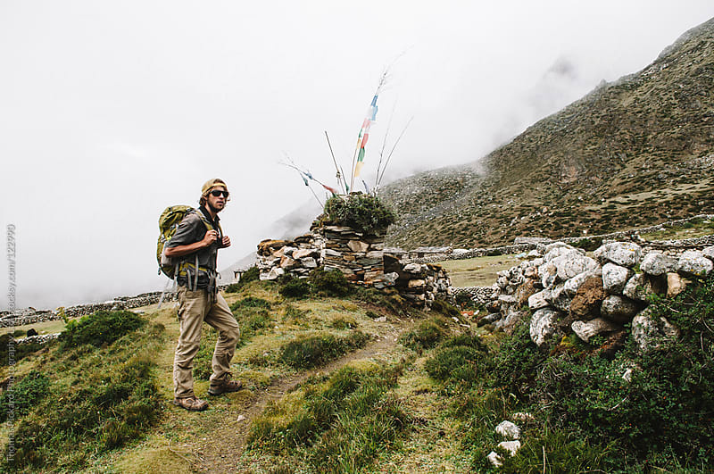 Male trekker pausing at a stone cairn, Everest Region, Sagarmatha National Park, Nepal. by Thomas Pickard for Stocksy United