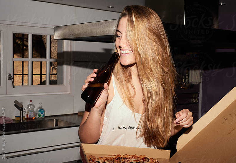 Young blondie drinking beer in the kitchen by Guille Faingold for Stocksy United