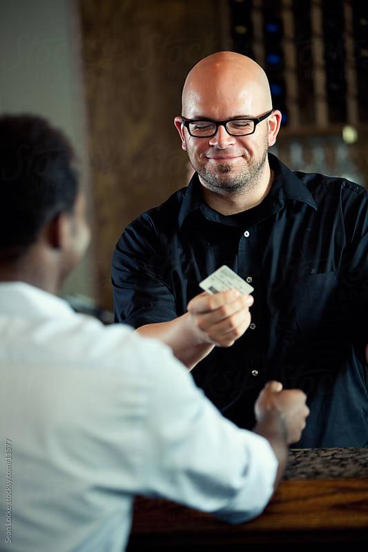 Bar: Bartender Examining Identification of Customer by Sean Locke for Stocksy United