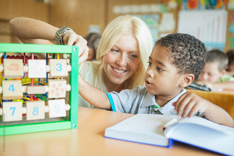 Learning Numbers: First Grader and His Teacher in Class by Lumina for Stocksy United