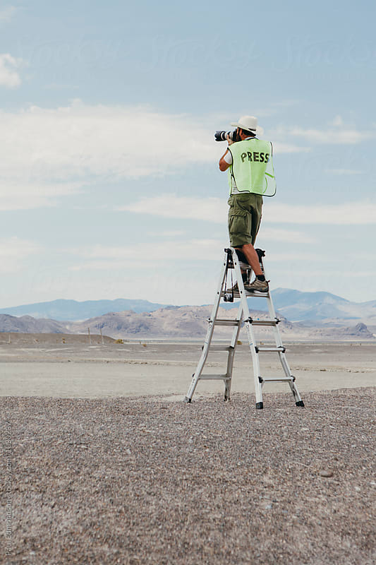 Professional photographer wearing Press vest, standing on ladder and pointing camera towards desert by Paul Edmondson for Stocksy United