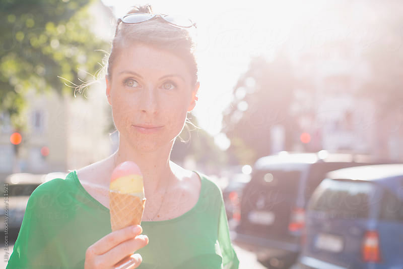Young woman, out and about in the city, having ice cream in a cone by Lilly Bloom for Stocksy United