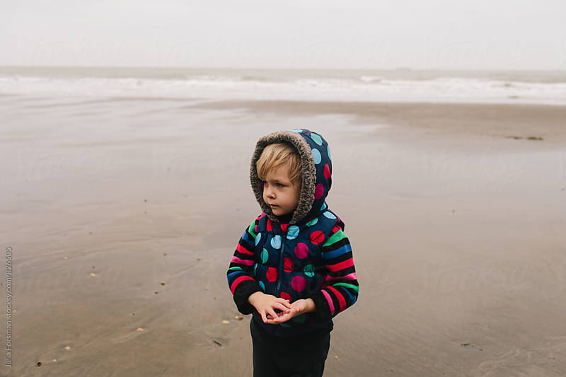 Girl in colourful winter clothes lost in thought on beach. by Julia Forsman for Stocksy United