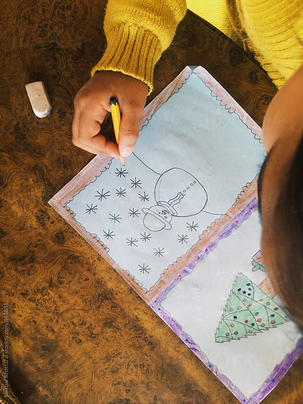 A young girl making christmas card. by Shikhar Bhattarai for Stocksy United