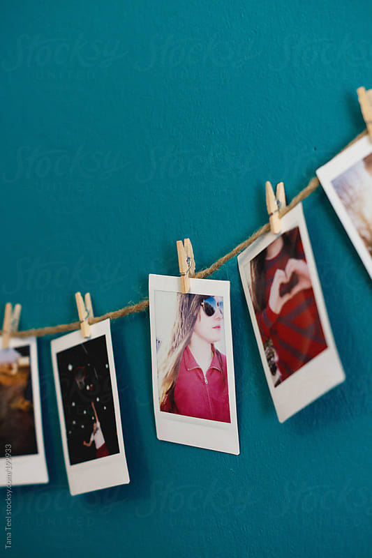 Mini polaroid pictures clipped to a string hang on a wall by Tana Teel for Stocksy United