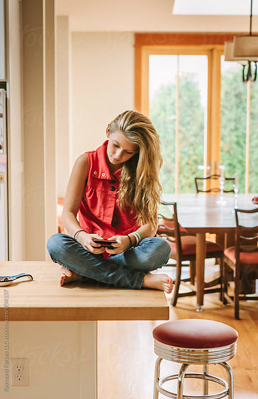 Teen Girl Texting at Home by Raymond Forbes LLC for Stocksy United
