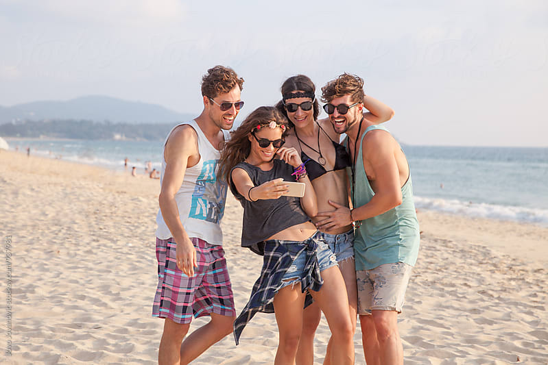 Four friends taking a selfie at the beach by Jovo Jovanovic for Stocksy United