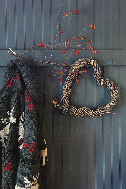 Vintage wool sweater hanging on coat hook with vine wreath by Sandra Cunningham for Stocksy United