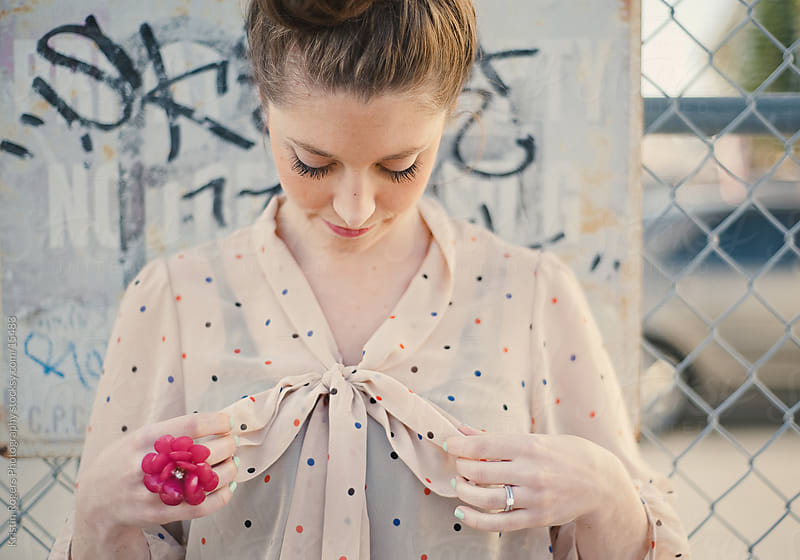 Young lady fixing her bow on spotted shirt with big pink ring by Kristin Rogers Photography for Stocksy United