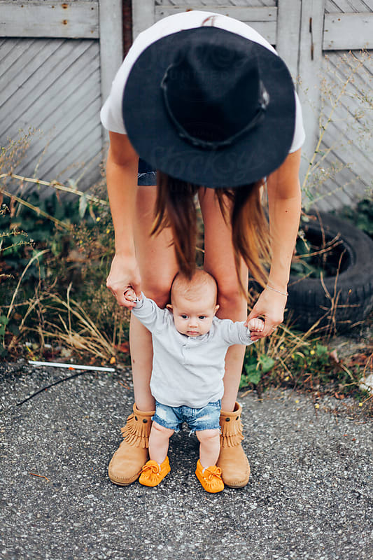 Young woman holding baby outdoors by Treasures & Travels for Stocksy United