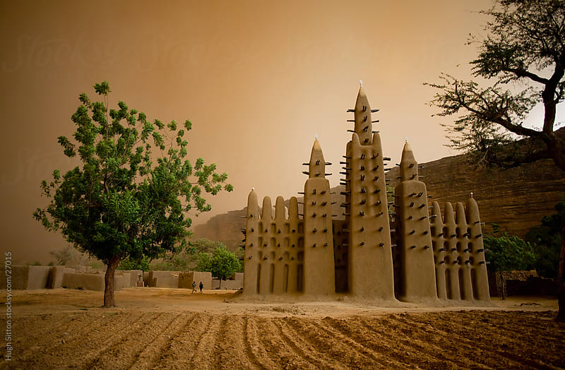 The mosque in Teli village during sand storm, Dogon Country, Mali by Hugh Sitton for Stocksy United