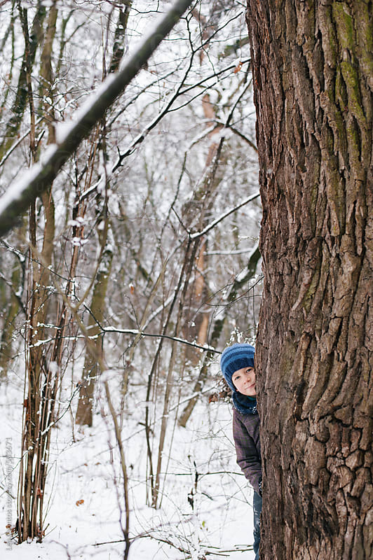 Boy playing hide-and-seek in a snowy forest. by Lea Csontos for Stocksy United