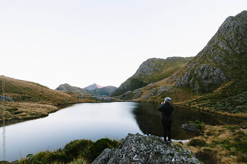 Woman looking over Adelaide Tarn Hut, Kahurangi National Park, New Zealand. by Thomas Pickard for Stocksy United