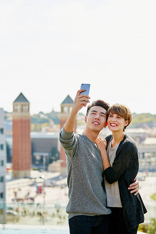 Happy Couple Talking Selfie In City by ALTO IMAGES for Stocksy United