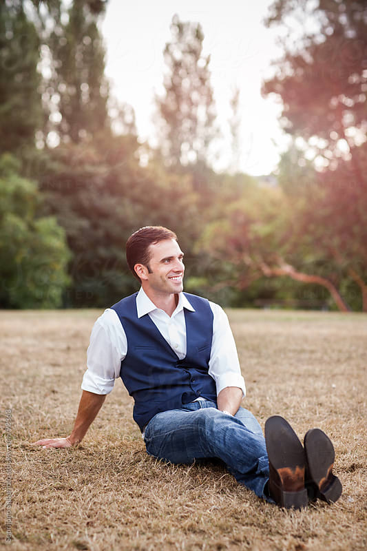 Happy handsome man sitting on the grass by Suprijono Suharjoto for Stocksy United