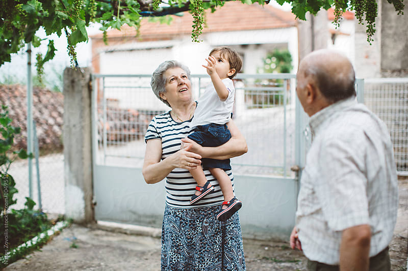 1 year old boy with his grandparent outdoor by Nasos Zovoilis for Stocksy United