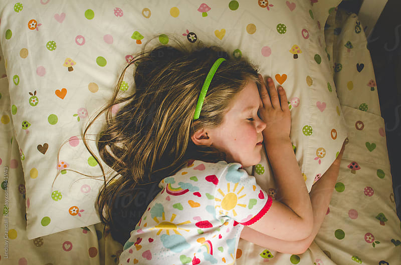 Little girl in pajamas sleeping in her bed by Lindsay Crandall for Stocksy United