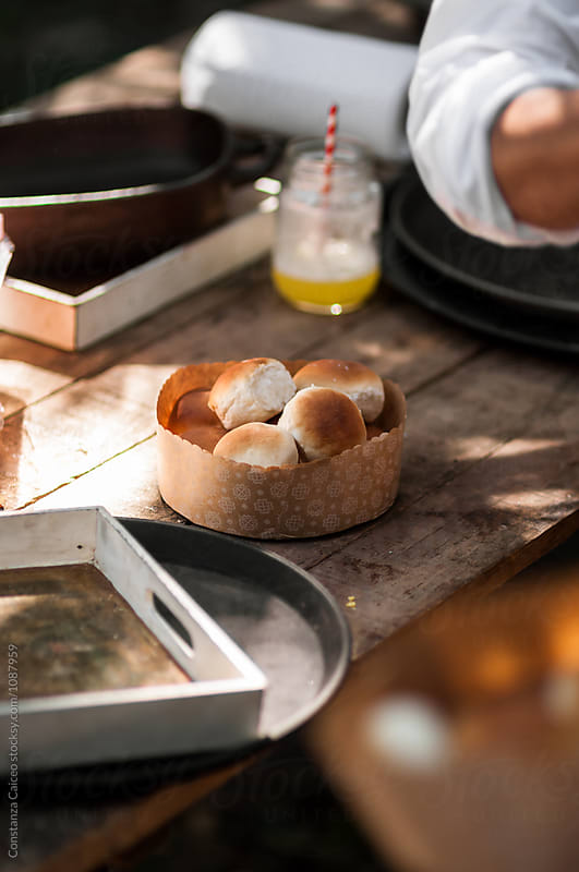 Homemade bread rolls on a rustic farm table by Constanza Caiceo for Stocksy United