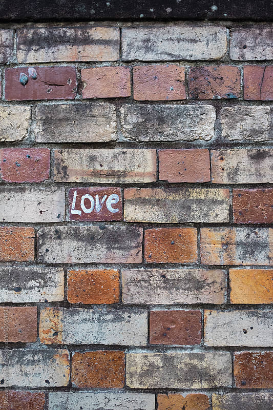 Brick wall with LOVE written on it by Rowena Naylor for Stocksy United
