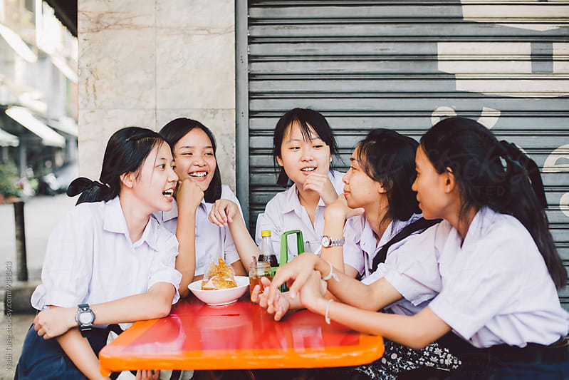 Asian high school girls sitting at street restaurant in Bangkok by Nabi Tang for Stocksy United