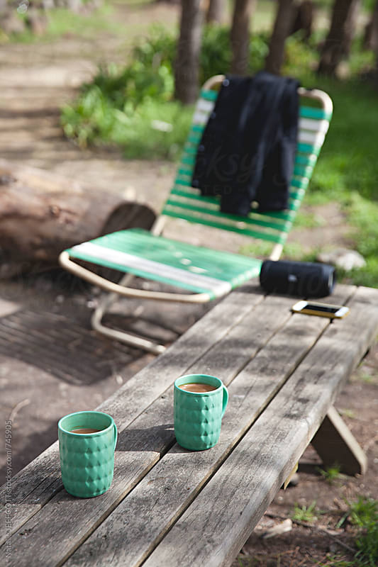 2 cups of coffee sitting on a wooden bench in the outdoor country side by Natalie JEFFCOTT for Stocksy United