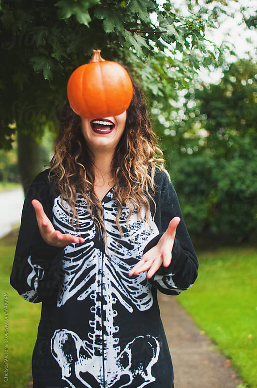 A young woman throwing a pumpkin in the air by Chelsea Victoria for Stocksy United