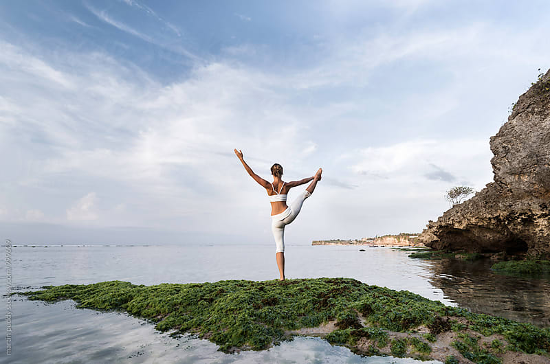 woman practicing yoga at sea shore by martin puddy for Stocksy United