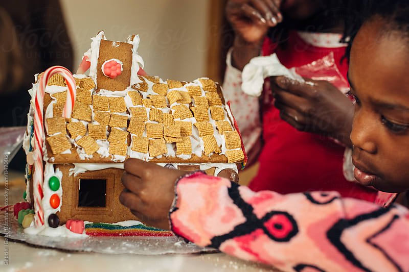 Young African American child working on a gingerbread house by Gabriel (Gabi) Bucataru for Stocksy United