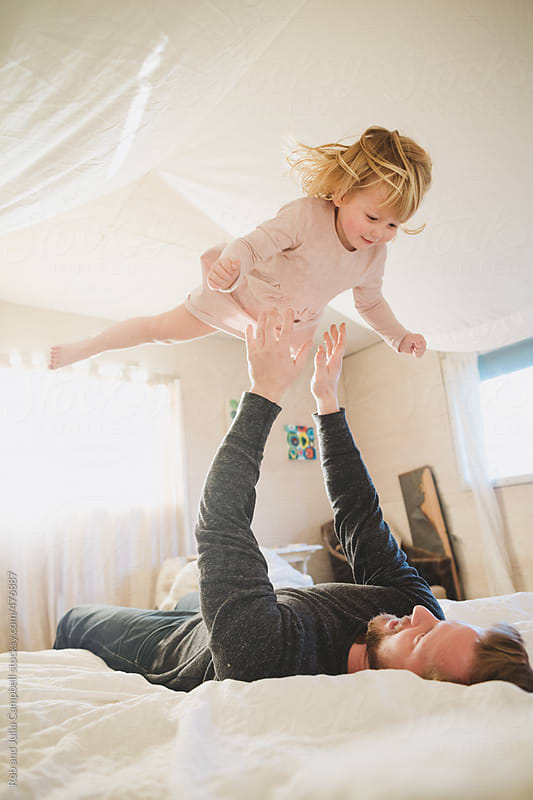 Young dad playing with toddler girl on bed - throwing her in air by Rob and Julia Campbell for Stocksy United